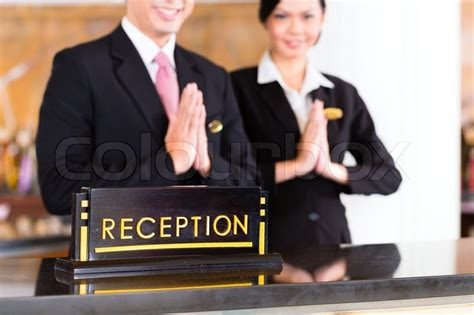 welcoming guests chinese asian reception team at luxury hotel front desk