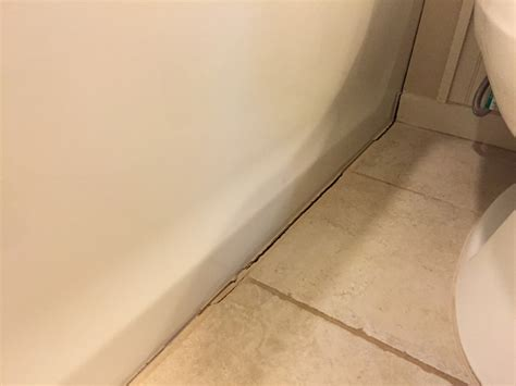 grout around bathtub installing caulk strip over cracked grout checking in