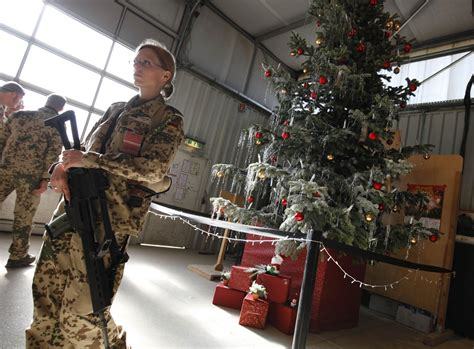 german soldier stands next to a christmas tree at army c