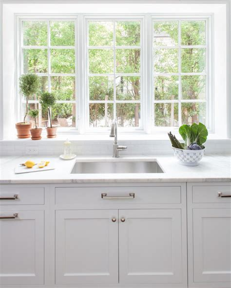 beautiful kitchen features white shaker cabinets paired