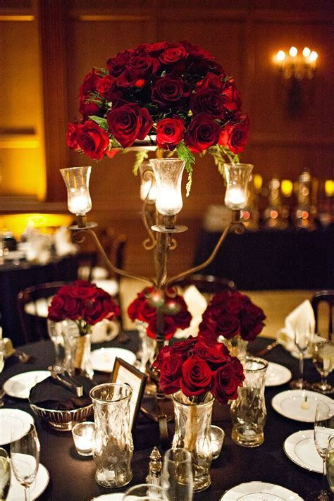 Dark red roses fill the table as they sit in vases and a