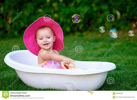 one girl one bathtub baby girl 1 2 year old taking bath with soap foam outdoors