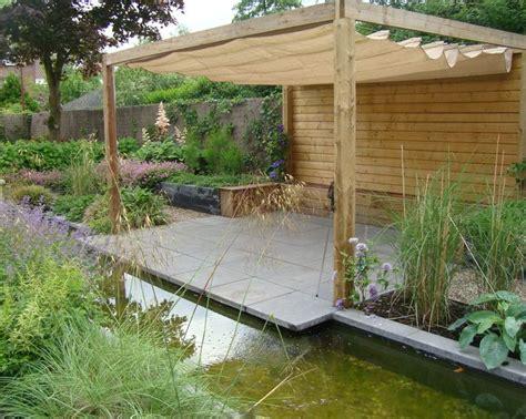 tuin met vijver vlonder en overkapping terras omringd door een vijver en diverse siergrassen