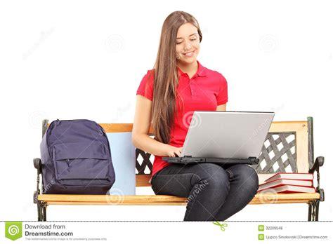 liberatoria banca studentessa sorridente che si siede su un banco di legno e