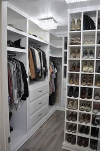 well organized walk in closet with white cabinets and