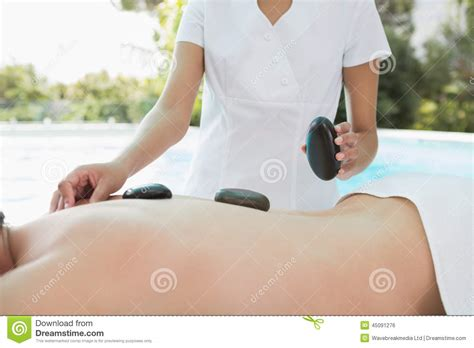 receiving section mid section of man receiving stone massage at spa center
