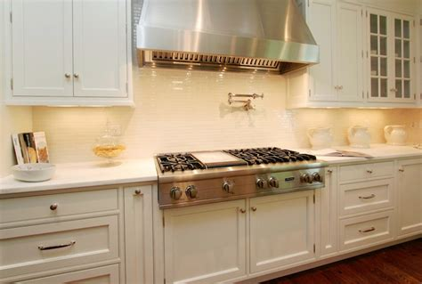 small white kitchen with steel hood stainless steel cooktop shelf cottage kitchen bhg