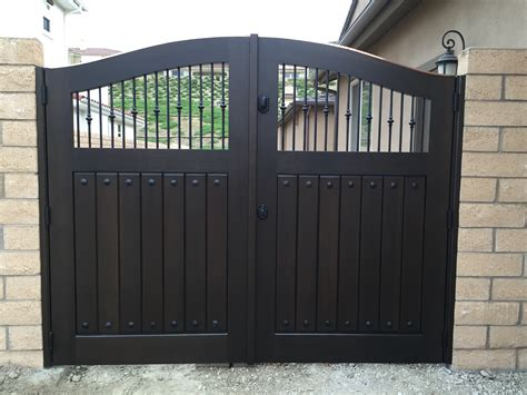 custom wood gate with swooping arch and decorative metal pickets by garden passages fencing