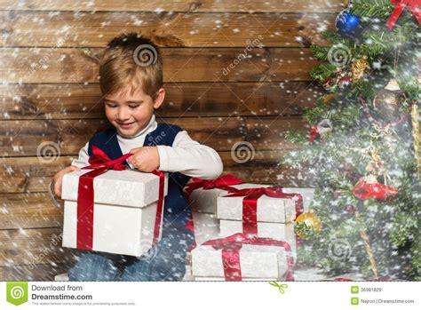 boy opening gift box  christmas tree royalty  stock images image