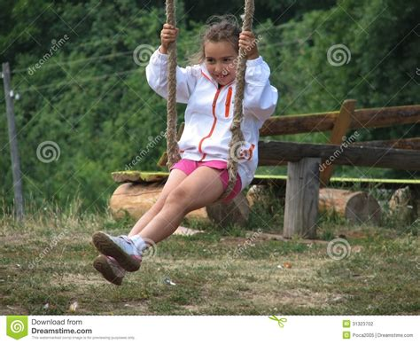 girl swinging girl swinging on a rope swing stock photography image