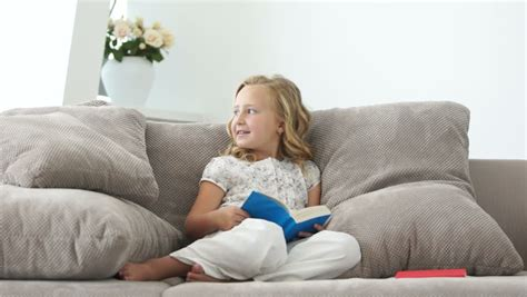 girl on the couch girl sitting on the couch and read a good book stock