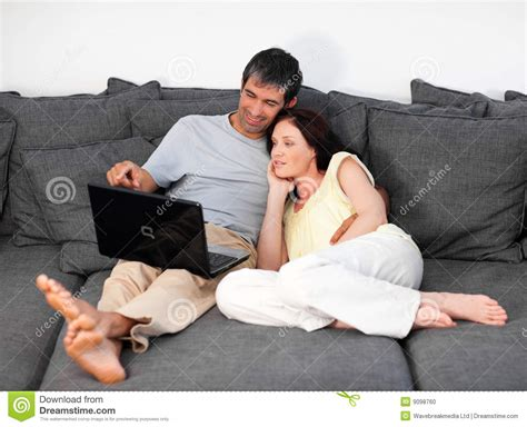 laying couch couple laying on couch with laptop stock photo image