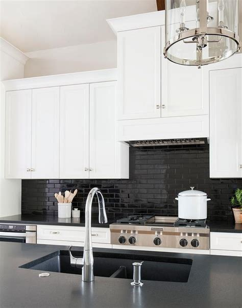 black subway tile kitchen backsplash kitchen vent hood hidden behind cabinets transitional