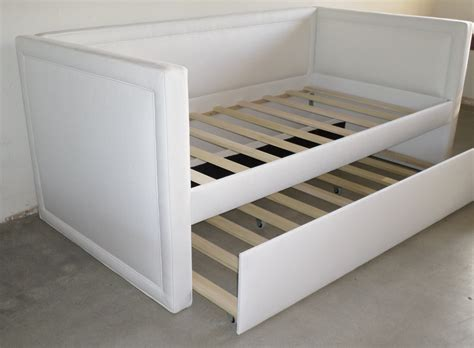 custom upholstered daybed w piping detail and rolling trundle