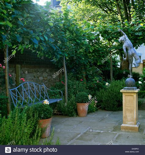 statue on plinth in paved walled garden with metal bench