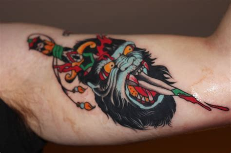 scary old color ink gorilla head pierced by knife