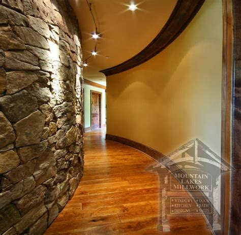 curved hallway with stone wall accent mountain view