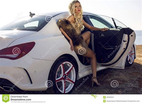 Auto Tuning Frauen by With Blond Hair Posing In Luxurious White Car Stock