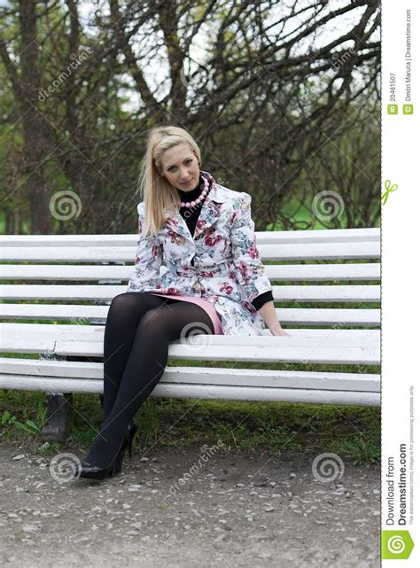 girl sitting on a bench blonde girl sitting on a park bench royalty free stock