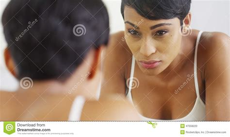 black woman looking in mirror black woman splashing face with water and looking in