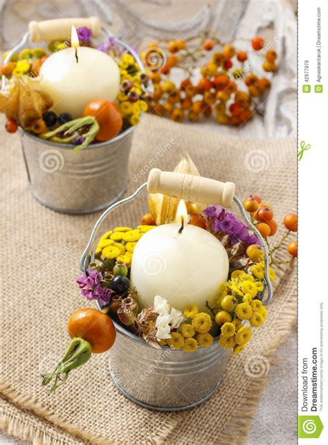candle holder decorated with autumn flowers and other