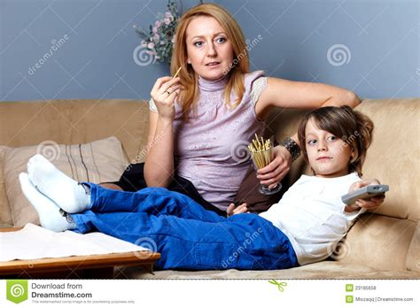 mom son couch mother and son sit on the sofa and watch tv royalty free