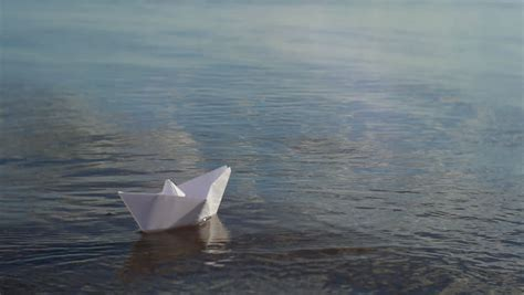 Floating Origami Boat - paper boat floating on the river stock footage