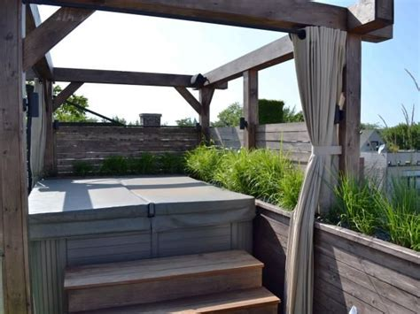 an outdoor hot tub and pergola sit on a wooden deck on