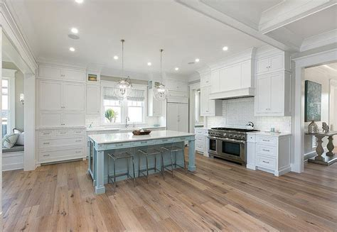 kitchen with wood floors and white cabinets white cabinets with powder blue kitchen island and sawn