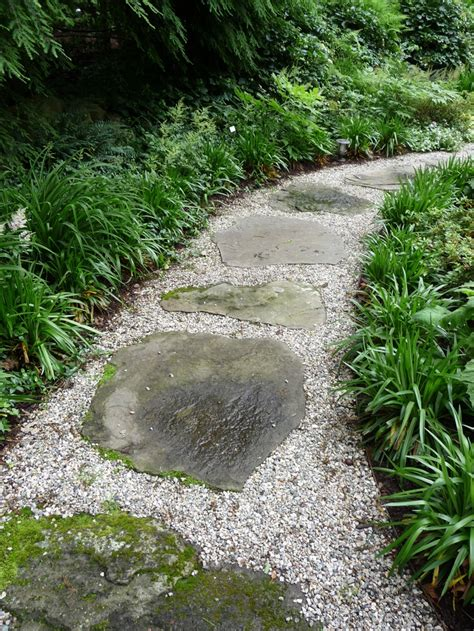 stepping stones set in pea gravel with steel edging strappy plants soften the edges walkways