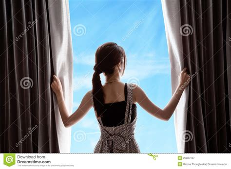 woman opening curtains young woman opening curtains and blue sky royalty free