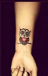 red owl with little daisy flower tattoos on wrist