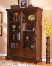 White Bookshelves With Drawers - high dark brown wooden bookcase with four shelves and glass doors placed on the light brown