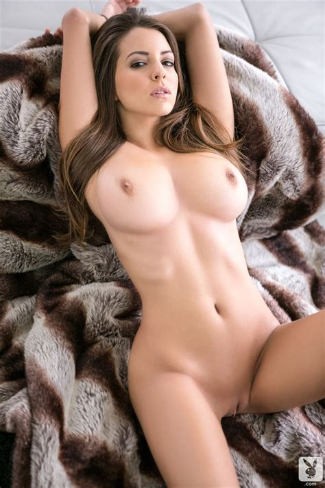 shelby chesnes cozies up on a fur rug naked indoors