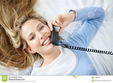 woman talking on cell phone in bed stock image f006 6900 stock photo young woman lying on bed while talking on