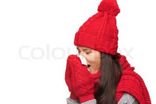 girl wearing warm winter hat, scarf and gloves blowing