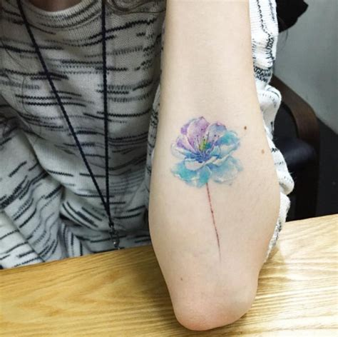 simple tiny watercolor like colored flower tattoo on