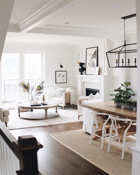 white wishbone chairs wood dining table white walls