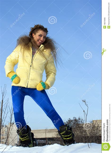 beautiful girl in a yellow jacket in winter stock image