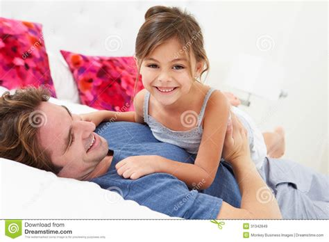 in daddys bed father and daughter lying in bed together royalty free