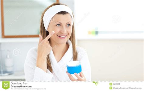women using the bathroom charming young woman using cream in the bathroom stock photography image 15875972