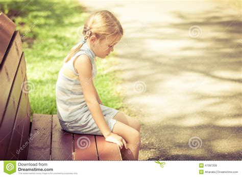 girl sitting on a bench sad little girl sitting on bench in the park stock photo