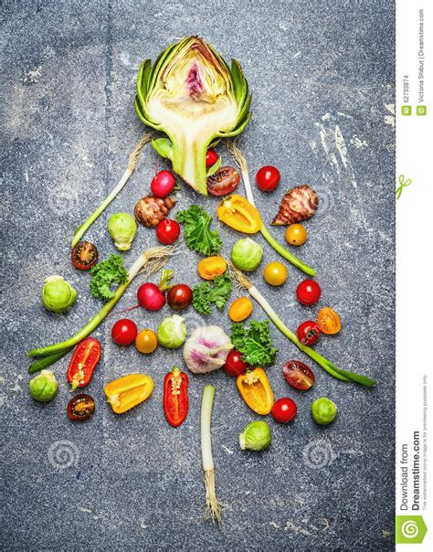 christmas tree made of fresh vegetables on gray rustic bac