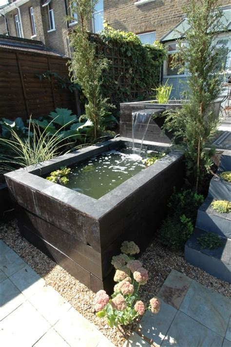raised railway sleeper pool and slate water feature
