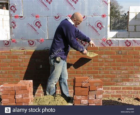builder construction worker working on a brick wall
