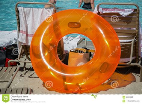 big inner big orange plastic inner poolside with deck chairs in