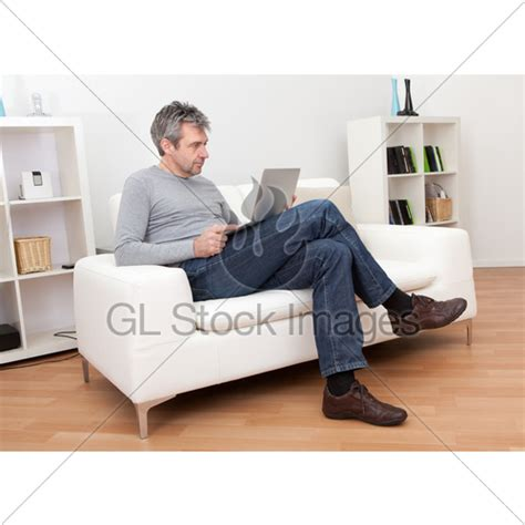 sitting in sofa senior man sitting in sofa and using laptop 183 gl stock images