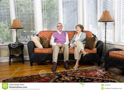 happy senior sitting on living room stock