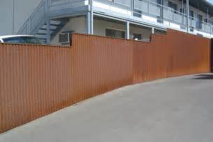 Rusted corrugated metal fence fence with corrugated steel panels