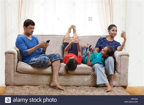 Livingroom Pc family using cell phones and digital tablets in living